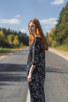 Młoda kobieta z długimi rudymi włosami w lnianej sukience w naturalnej lokalizacji w tle