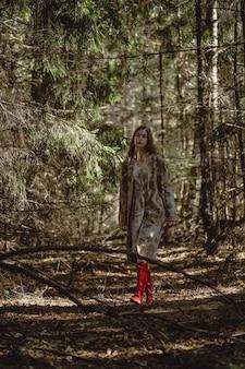 Młoda kobieta z długimi rudymi włosami w lnianej sukience zbierając grzyby w lesie