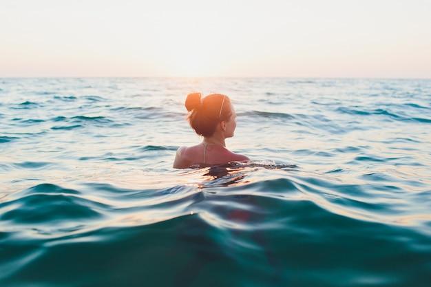 Młoda kobieta z długimi włosami, blondynką, topless, siedząca w wodzie i trzymająca w dłoni top bikini w promieniach słońca.