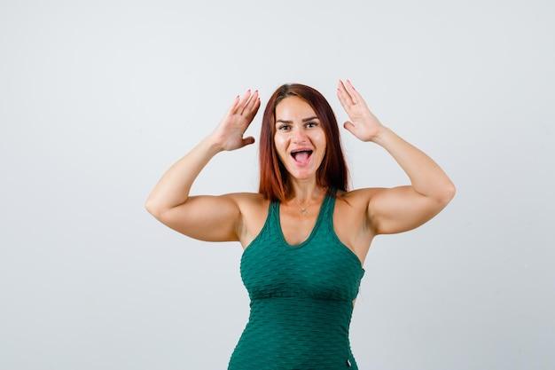 Młoda kobieta z długimi włosami i podniesionymi rękami