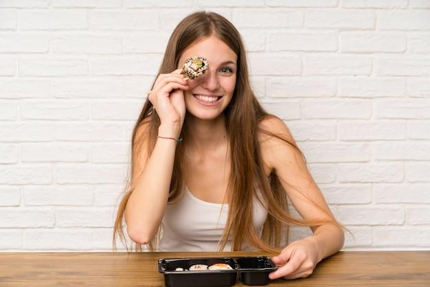 Młoda kobieta z długimi włosami jedzenia sushi