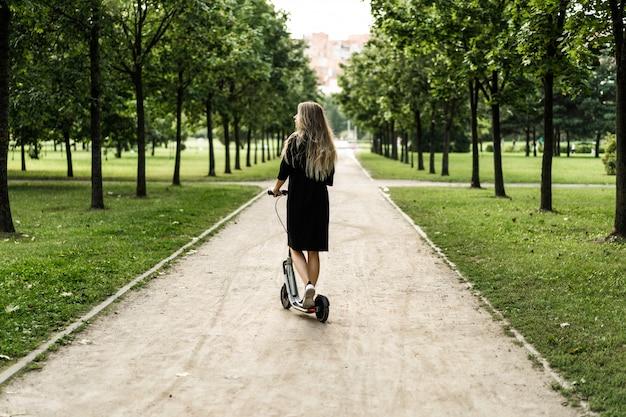 Młoda kobieta z długimi włosami na skuter elektryczny. dziewczyna na elektrycznej skuterze.