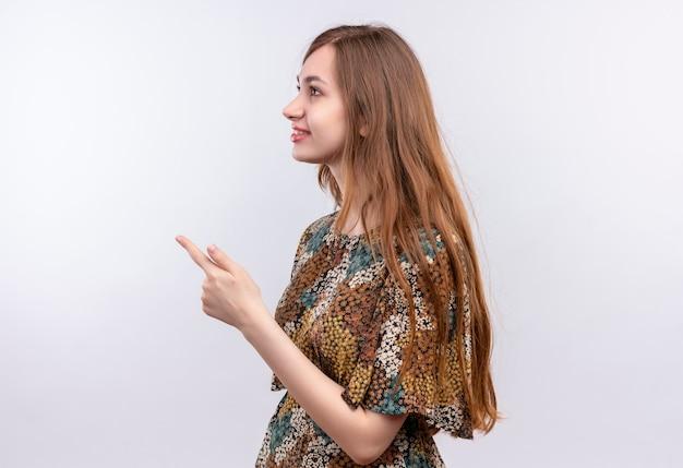 Młoda kobieta z długimi włosami na sobie kolorową sukienkę stojącą bokiem, wskazując palcem na bok, stojąc na białej ścianie