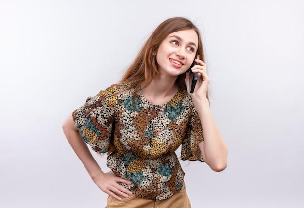 Młoda kobieta z długimi włosami na sobie kolorową sukienkę uśmiechnięty, rozmawiając na telefon komórkowy stojąc na białej ścianie