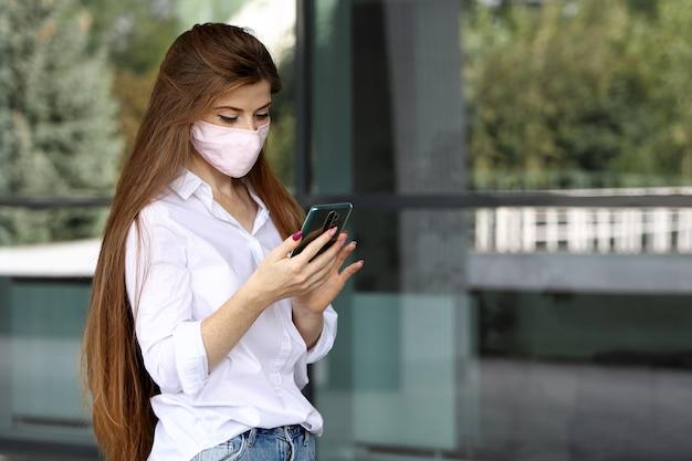 Młoda kobieta z długimi włosami, nosząca maskę ochronną, przegląda i przewija w smartfonie