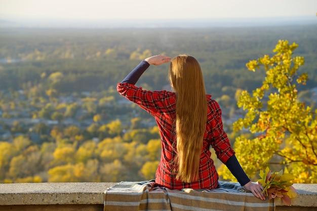 Młoda kobieta z długimi włosami siedzi na wzgórzu z widokiem na miasto.