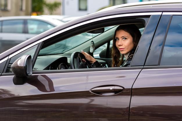 Młoda kobieta z długimi włosami siedzi za kierownicą samochodu i wygląda przez okno