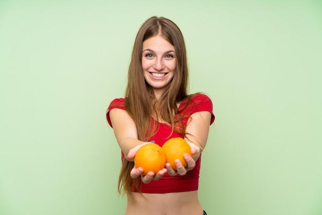Młoda kobieta z długimi włosami, trzymając pomarańczę
