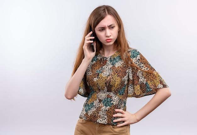 Młoda kobieta z długimi włosami ubrana w kolorową sukienkę rozmawia przez telefon komórkowy z marszczącą brwią twarz stojącą na białej ścianie