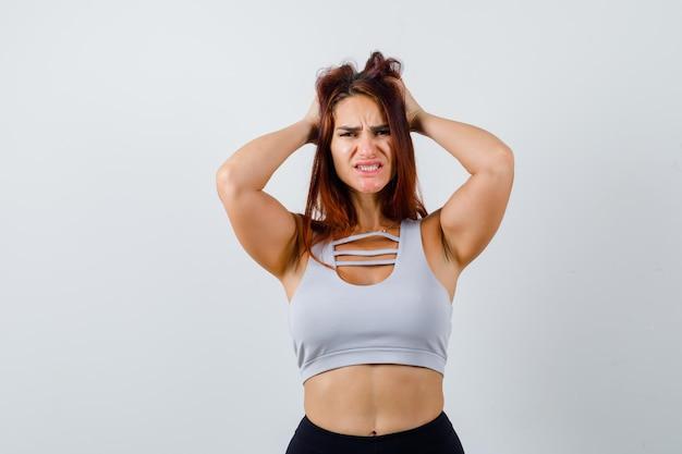 Młoda kobieta z długimi włosami ubrana w odzież sportową