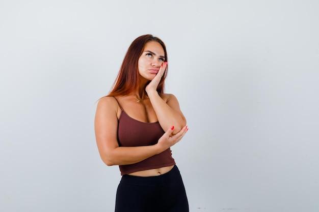Młoda kobieta z długimi włosami w brązowym topie