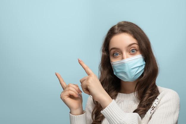 Młoda kobieta z długimi włosami w masce medycznej wskazuje róg ekranu dwoma palcami.