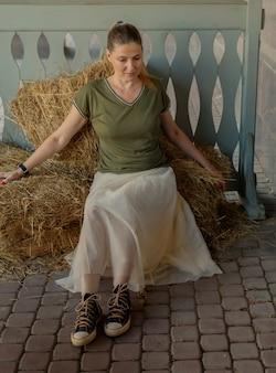Młoda kobieta z długimi włosami, w pełnej spódnicy, podkoszulku, latem siedzi na słomie w ekologicznej kawiarni. portret kobiety w naturalnym, wiejskim otoczeniu. pojęcie ekoturystyki ekologicznej.