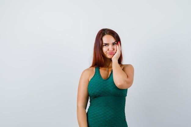 Młoda kobieta z długimi włosami w zielonym bodycon