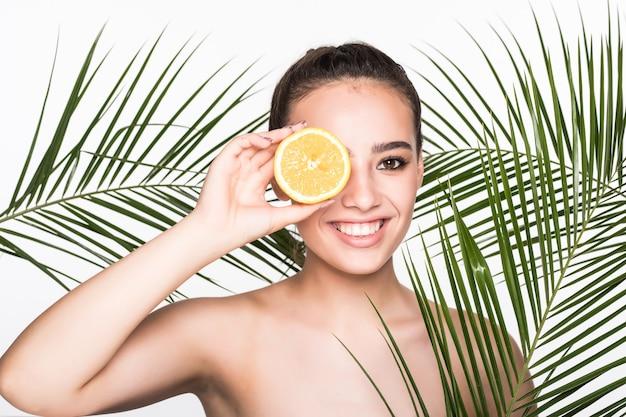 Młoda kobieta z doskonałej skóry trzymając w ręku owoce cytrusowe otoczony palmami pozostawia odizolowane na białej ścianie