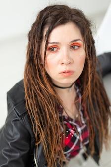 Młoda kobieta z dredami i jaskrawym makijażem