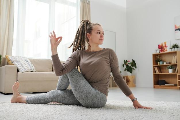 Młoda kobieta z dredami siedzi na podłodze w jednej z pozycji jogi, rozciągając mięśnie ramion i nóg