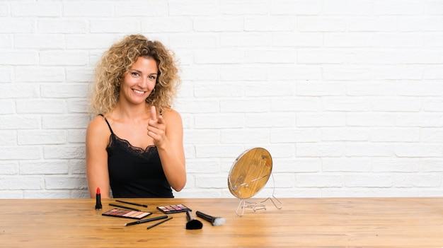 Młoda kobieta z dużą ilością pędzla do makijażu w tabeli wskazuje palcem na ciebie