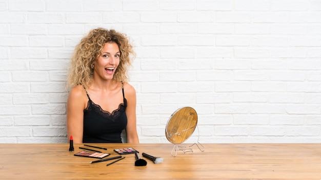 Młoda kobieta z dużą ilością pędzla do makijażu w tabeli z niespodzianką wyraz twarzy