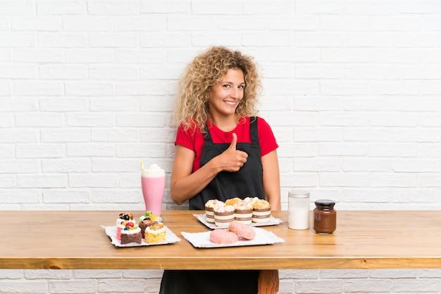 Młoda kobieta z dużą ilością różnych mini ciastek w tabeli podając kciuki gest