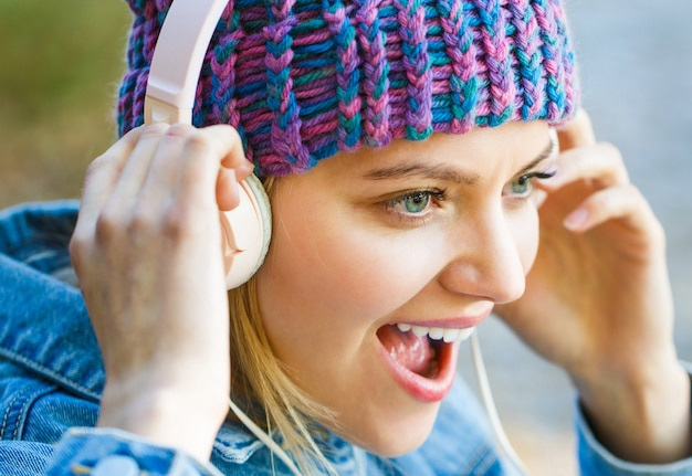 Młoda kobieta z dużymi słuchawkami wesoła dziewczyna radująca się słuchaniem muzyki w słuchawkach uśmiechnięta