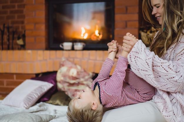 Młoda kobieta z dzieckiem. mama i syn żartują, bawią się przy kominku.