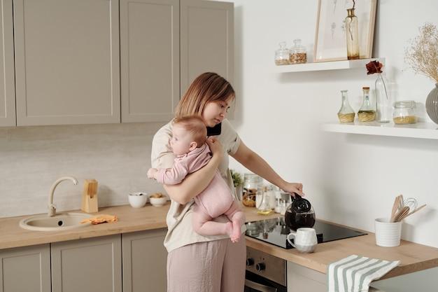 Młoda kobieta z dzieckiem nalewa herbatę do kubka i rozmawia na smartfonie