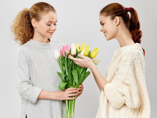Młoda kobieta z dzieckiem pozuje w studiu z kwiatami