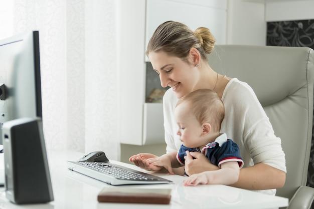 Młoda kobieta z dzieckiem pracuje w domu i korzysta z komputera