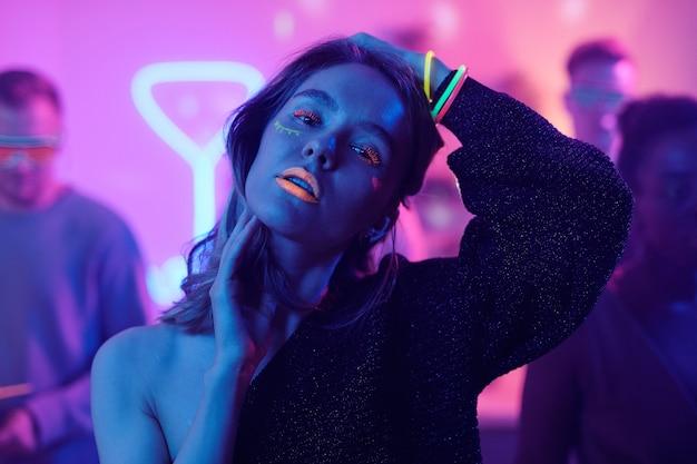 Młoda kobieta z efektownym neonowym makijażem, patrząca na ciebie, stojąc przed kamerą na tle swoich przyjaciół, tańczących i cieszących się imprezą