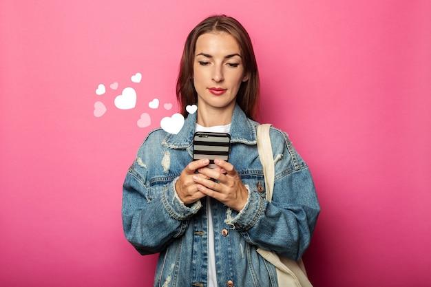Młoda kobieta z eko torba patrząc na telefon z naciskiem na różowej ścianie.