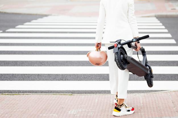 Młoda kobieta z elektryczną hulajnogą i kaskiem na przejściu dla pieszych w mieście