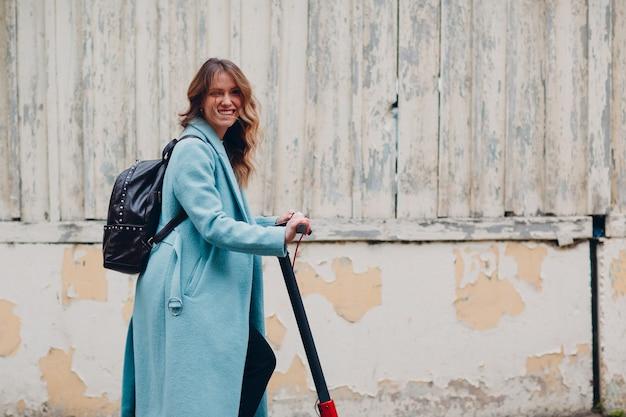 Młoda kobieta z elektryczną hulajnogą w niebieskim płaszczu w mieście