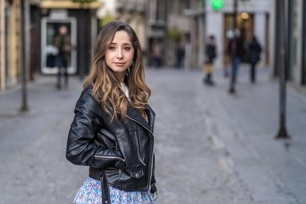 Młoda kobieta z falą we włosach ubrana w czarną kurtkę w mieście