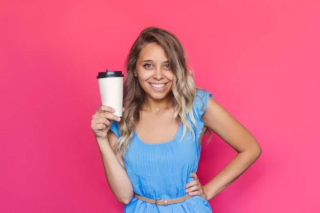 Młoda Kobieta Z Falującymi Włosami Trzyma Białą Papierową Filiżankę Kawy Lub Herbaty Na Różowym Tle Premium Zdjęcia