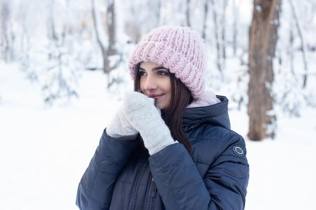 Młoda kobieta z filiżanką gorącej herbaty w śnieżnym parku w zimie