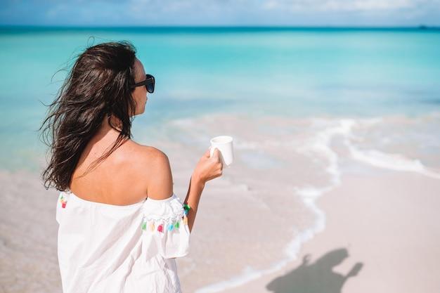Młoda kobieta z filiżanką gorącej kawy cieszy się wakacje