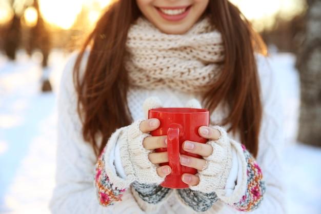 Młoda kobieta z filiżanką gorącej kawy na zewnątrz w zimowy dzień, zbliżenie