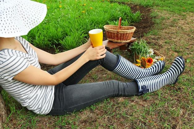 Młoda kobieta z filiżanką kawy, siedząc na łące na zewnątrz