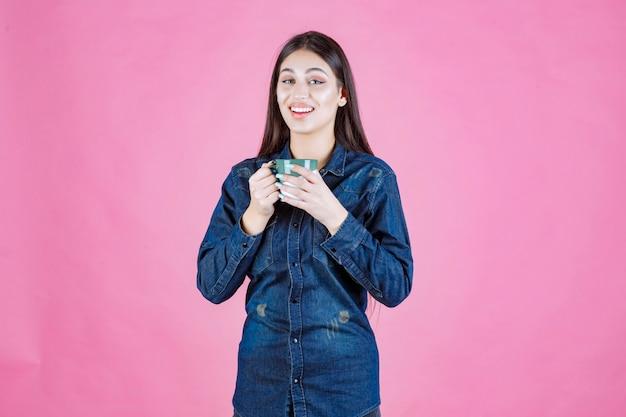 Młoda kobieta z filiżanką kawy uśmiechnięta i pozytywna