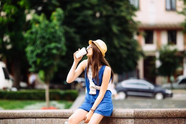 Młoda kobieta z filiżanką kawy w pobliżu fontanny