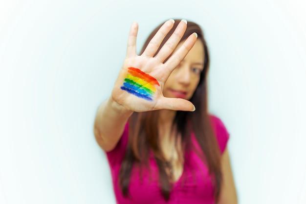 Młoda kobieta z flagą lgbti namalowaną na jej dłoni uśmiechając się.