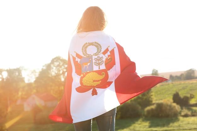 Młoda kobieta z flagą peru na zewnątrz