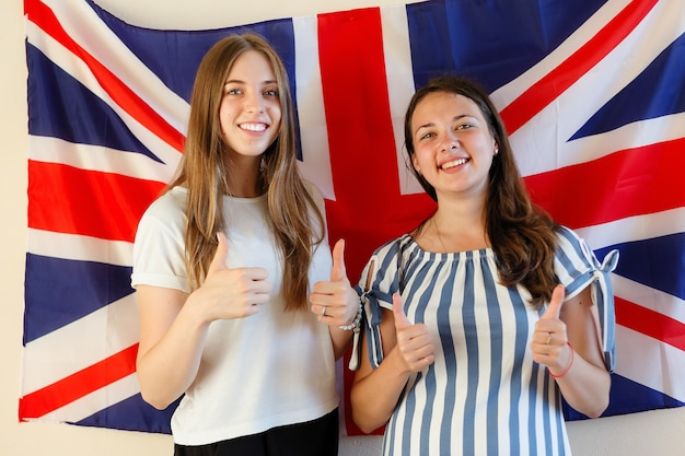Młoda kobieta z flagami krajów anglojęzycznych. angielska studentka z brytyjską flagą w tle. angielski, ucz się, studiuj.