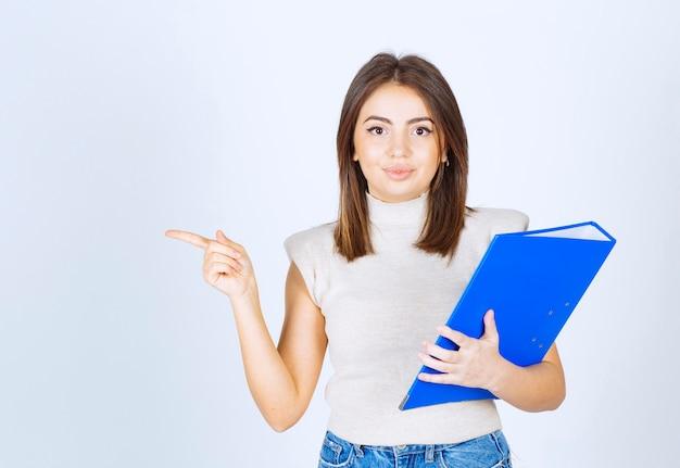 Młoda kobieta z folderem wskazującym palcem wskazującym.