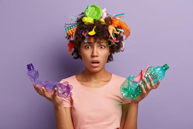 Młoda kobieta z fryzurą afro i plastikowymi odpadami we włosach