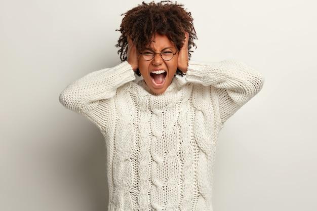 Młoda kobieta z fryzurą afro na sobie biały sweter