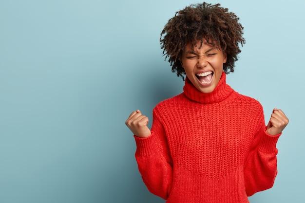 Młoda kobieta z fryzurą afro na sobie czerwony sweter