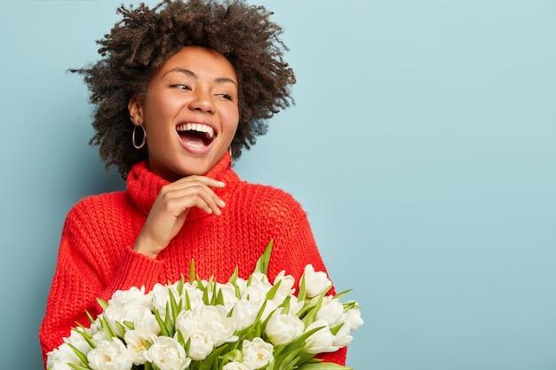 Młoda kobieta z fryzurą afro trzymając bukiet białych kwiatów
