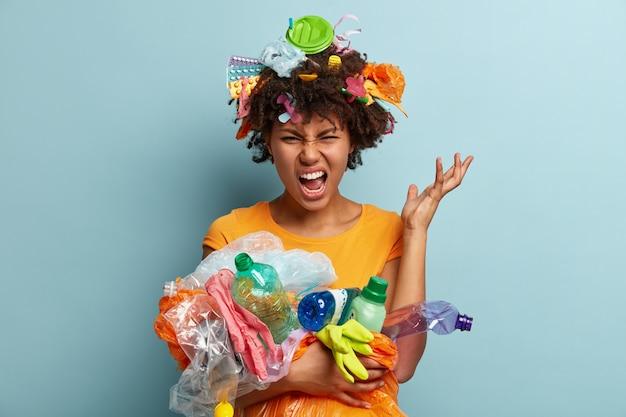 Młoda kobieta z fryzurą afro trzymając torbę z plastikowymi odpadami